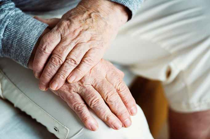 selective focus photography of left hand on top of right hand on white pants